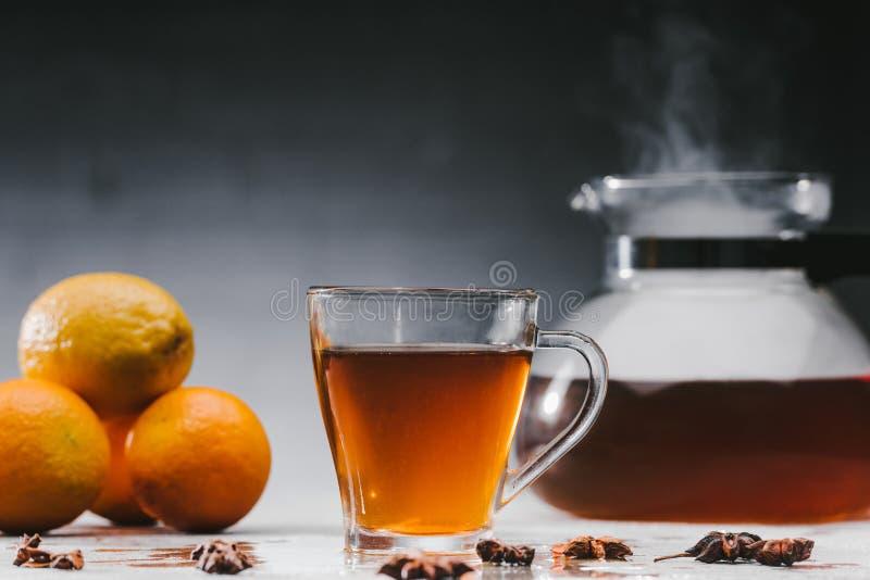 Чашка горячего черного чая с цитрусовыми фруктами стоковая фотография