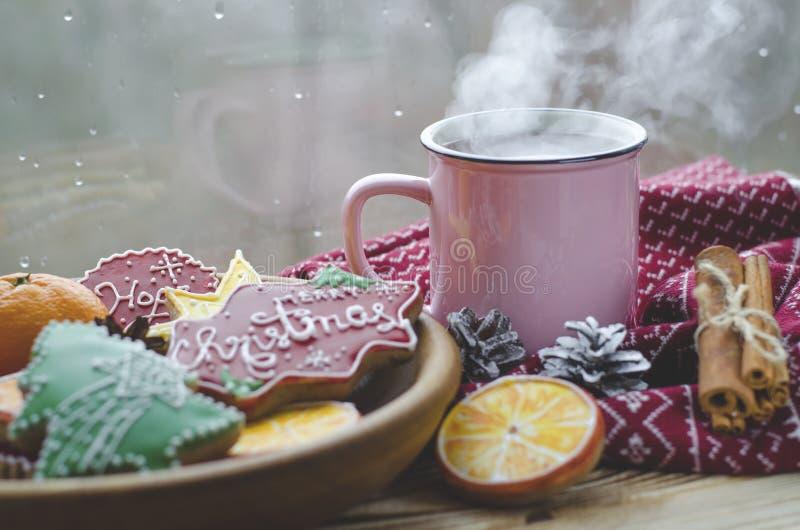 Чашка горячих стоек чая на деревянном столе рядом с деревянной плитой на которой печенья пряника сделанные из апельсина стоковые изображения