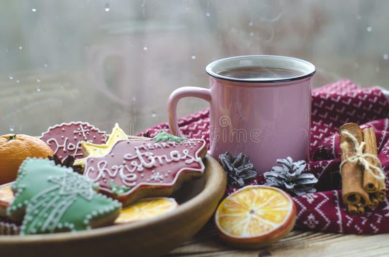 Чашка горячих стоек чая на деревянном столе рядом с деревянной плитой на которой печенья пряника сделанные из апельсина стоковые фотографии rf
