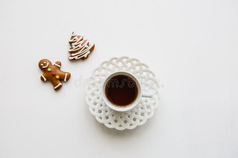 Чашка душистого и вкусного травяного или черного чая на белой поверхности Близрасположенные пряник или печенья рождества лож стоковое фото