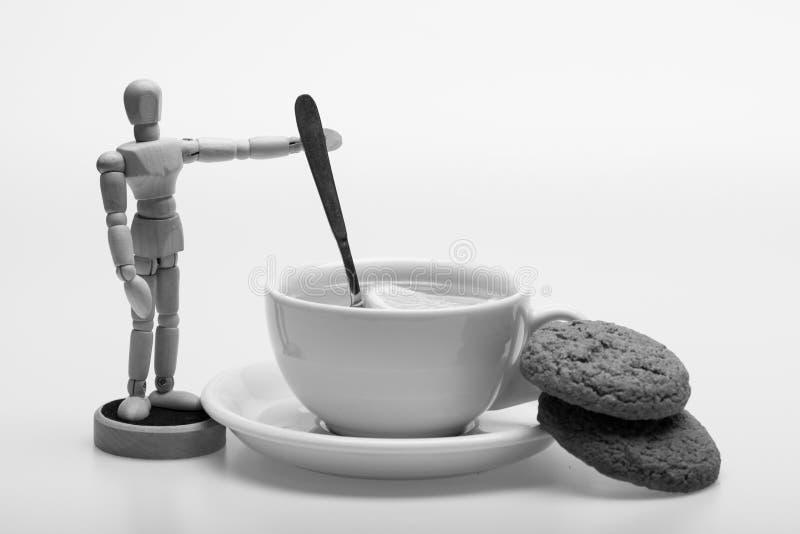 Чашка зеленого чая и humanlike игрушки шевеля ее Чай с кусками лимона и ложка как весло стоковые фотографии rf