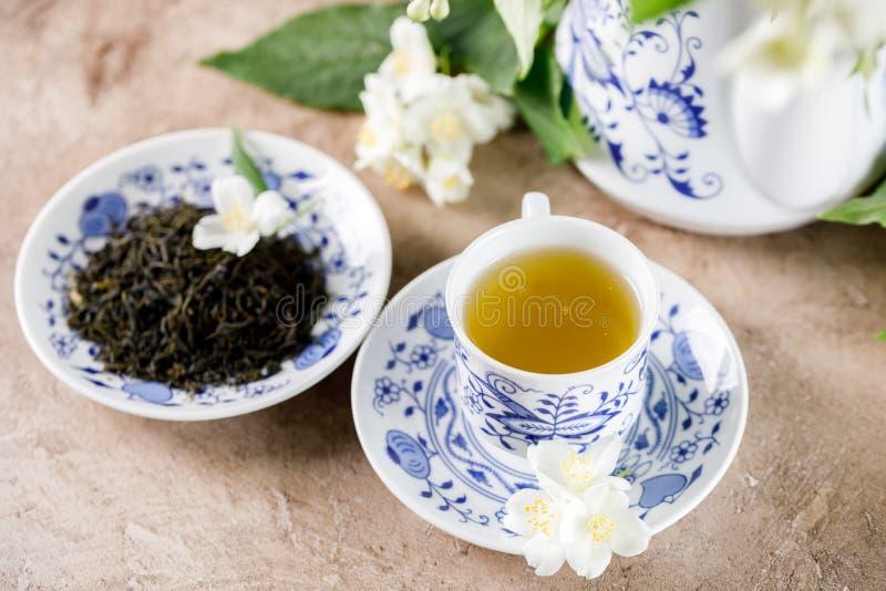 Чашка зеленого чая с вкусом жасмина и поддонника с сухими листьями чая стоковые фотографии rf