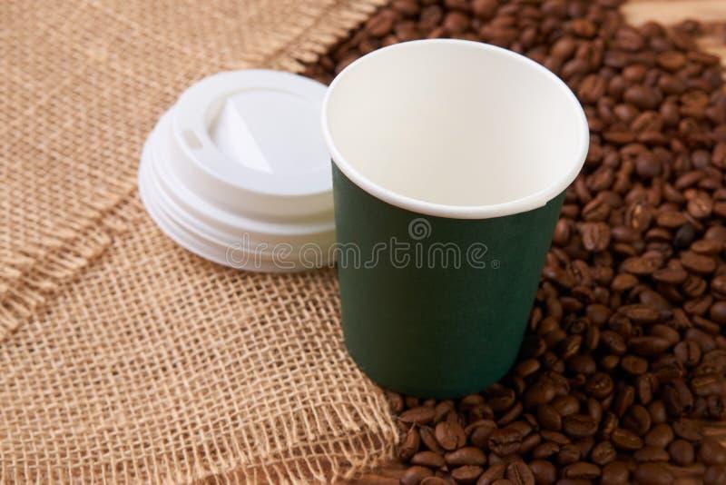 Чашка зеленой книги и кофейные зерна на деревянном столе стоковое фото