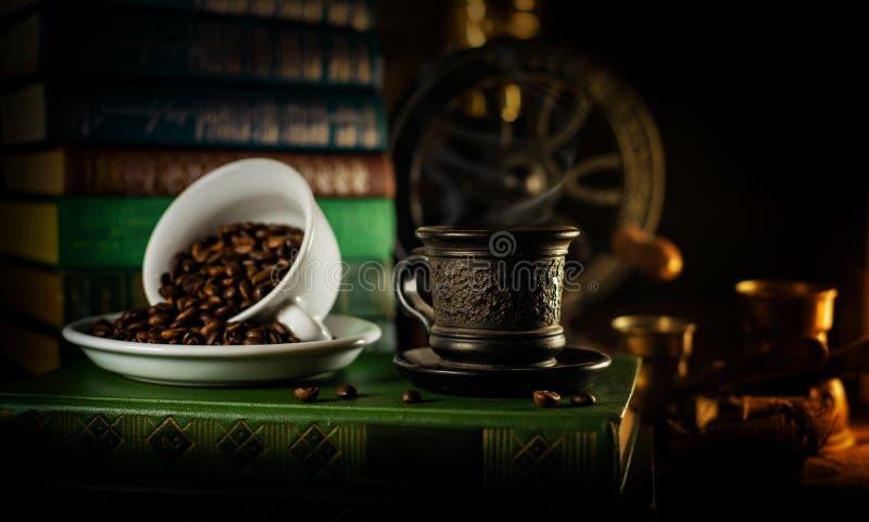 Чашка испаряться горячий кофе и другое одно с кофейными зернами Атмосфера старой библиотеки с книгами вокруг и точильщика на темн стоковые фото