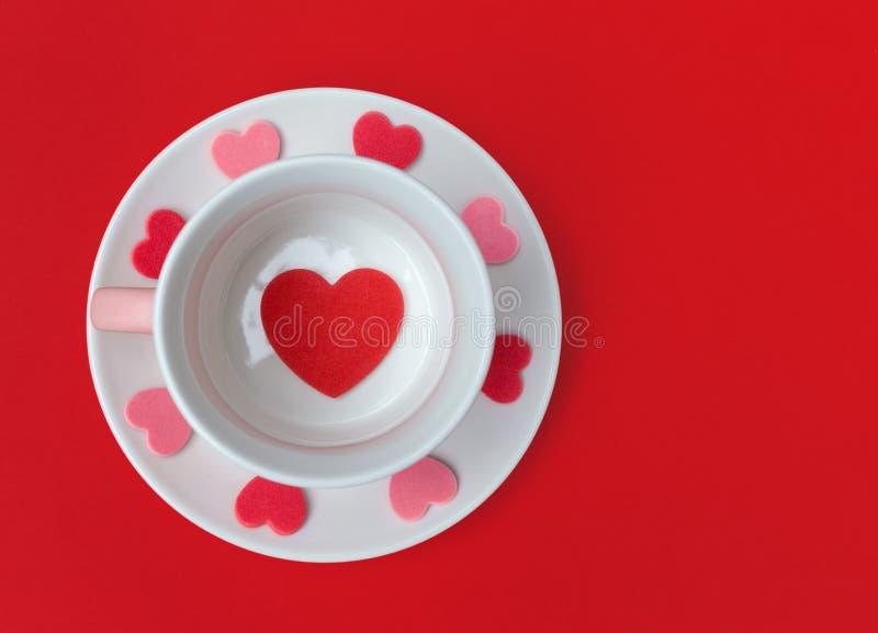 Чашка и поддонник чая с сердцами любов на красной предпосылке Квартира кладет с космосом экземпляра стоковые изображения rf