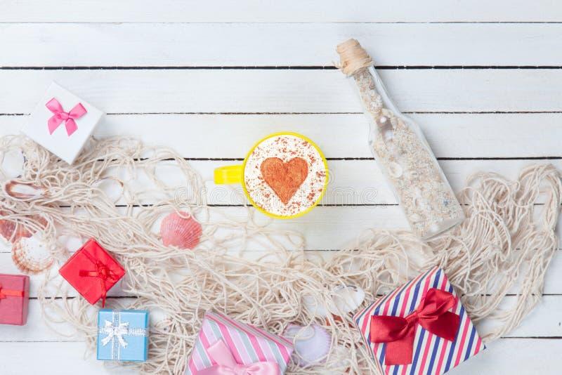 Чашка и подарочная коробка с сетью и бутылкой стоковые изображения