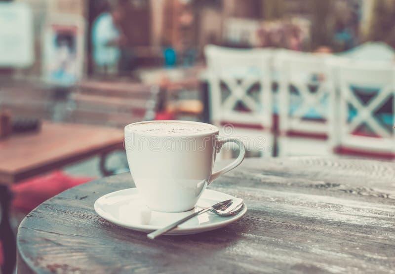 Чашка капучино на старом темном деревянном столе в кафе улицы стоковые изображения rf