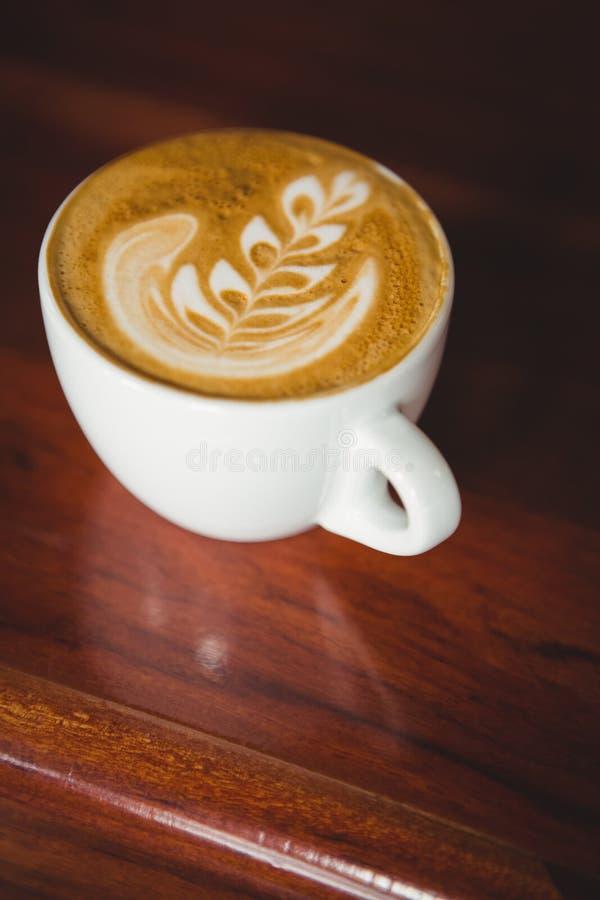 Чашка капучино с искусством кофе на счетчике стоковое изображение rf