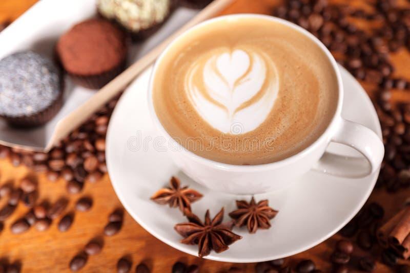 Чашка капучино с искусством latte на деревянном столе с кофейными зернами, анисовке, циннамоне Тратить время с чашкой кофе стоковое изображение