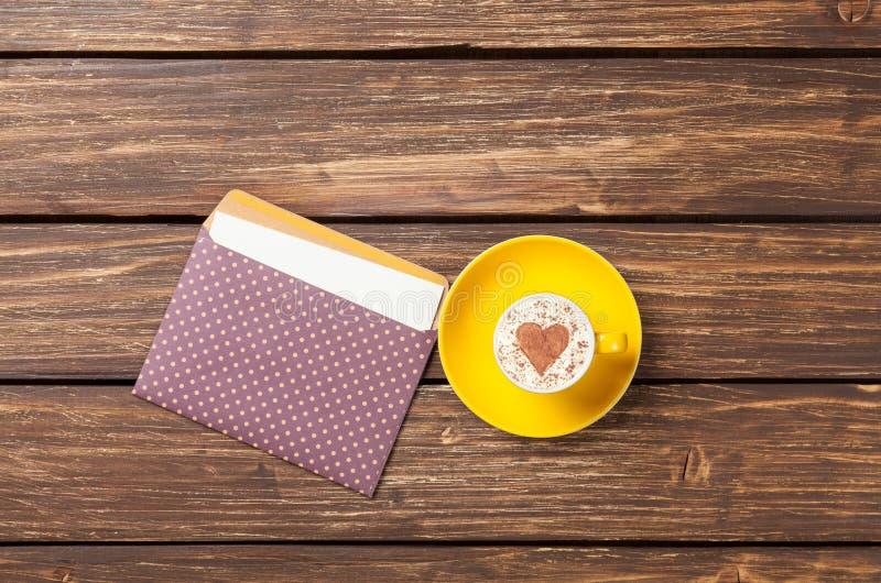 Чашка капучино с формой и конвертом сердца стоковые фотографии rf