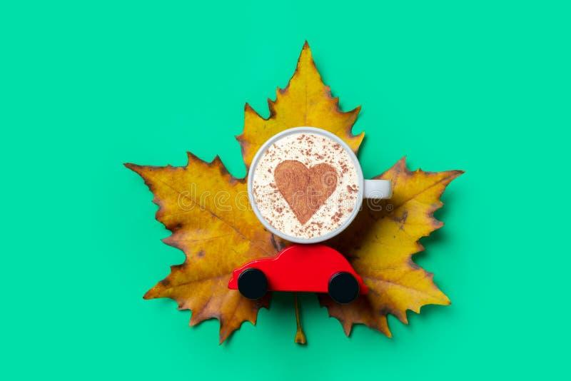 Чашка капучино с формой сердца и автомобилем игрушки стоковые изображения