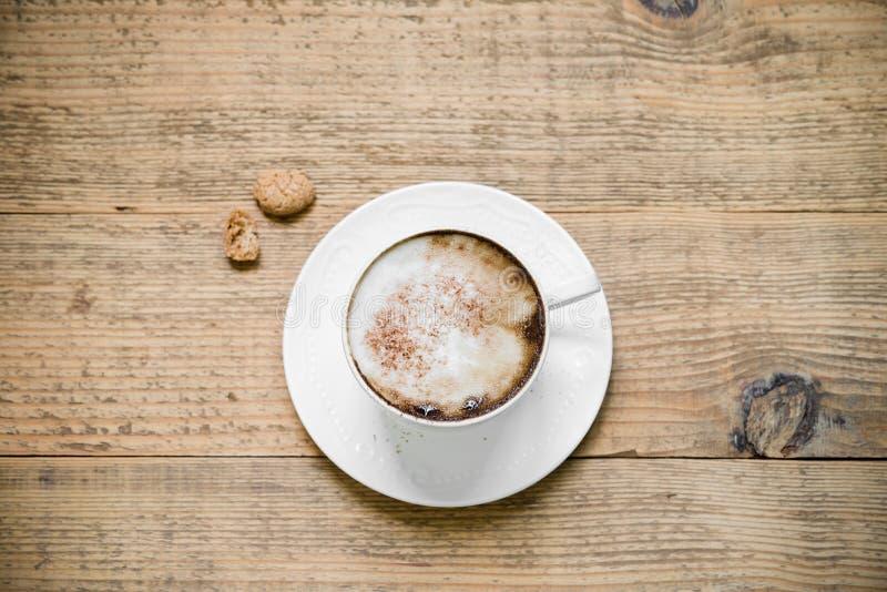 Чашка капучино с biscotti на таблице woode стоковые изображения rf