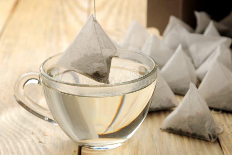 Чашка кипятка и пирамиды пакетика чая понижена в чашку Конец-вверх На деревянной таблице стоковые фотографии rf