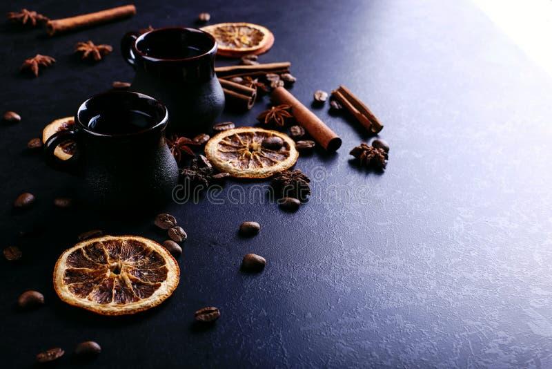 Чашка кофе, анисовка звезды, циннамон, высушенный апельсин и кофейные зерна на темном countertop кухни Душистые специи для напитк стоковая фотография