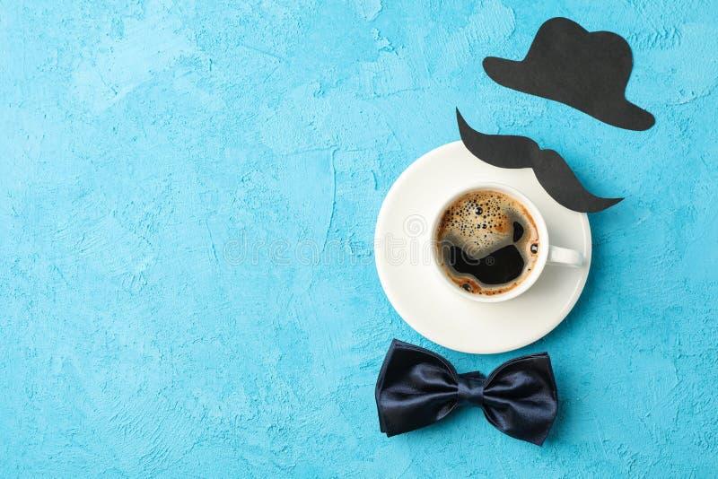 Чашка кофе, бабочка, декоративный усик и шляпа на голубой предпосылке, космосе для текста стоковая фотография