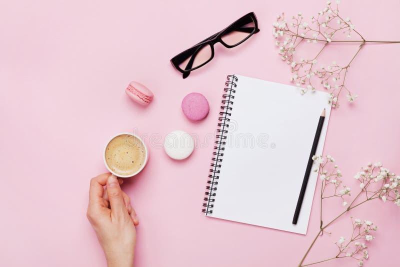 Чашка кофе владением руки женщины, macaron торта, чистая тетрадь, eyeglasses и цветок на розовой таблице сверху Женский работая с стоковое изображение rf