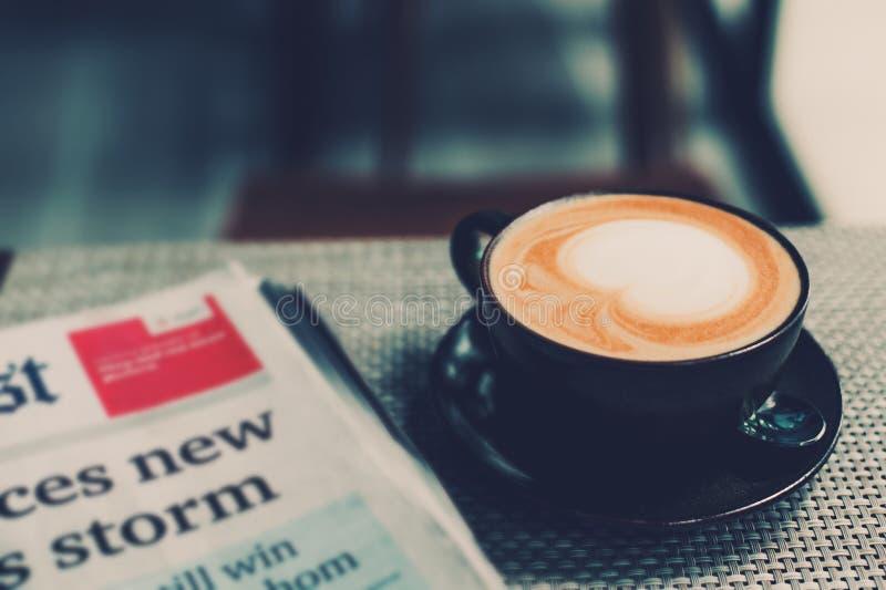 Чашка кофе и газета кофе на деревянном столе стоковые изображения