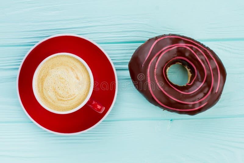 Чашка кофе и донут на деревянной предпосылке стоковое изображение rf