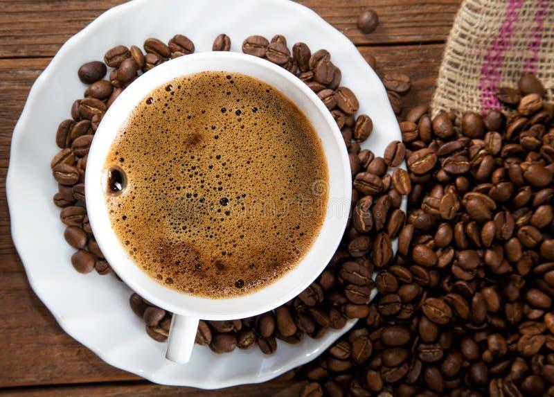 Чашка кофе и зерно на таблице стоковые изображения