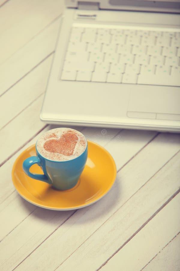 Чашка кофе и компьтер-книжка стоковая фотография rf