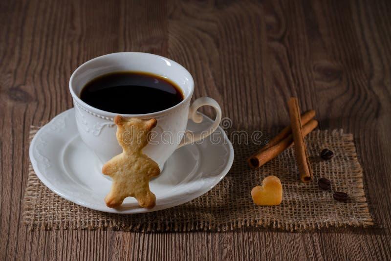 Чашка кофе и печенья как медведь и сердце с циннамоном, кофейными зернами на деревянном столе стоковая фотография rf