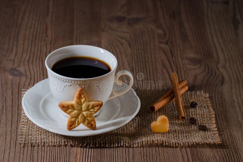 Чашка кофе и печенья любят звезда и сердце с циннамоном, кофейными зернами на деревянном столе стоковое фото rf