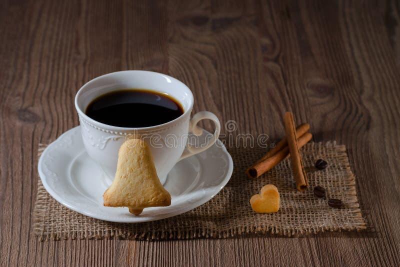Чашка кофе и печенья любят колокол и сердце с циннамоном, кофейными зернами на деревянном столе стоковое изображение