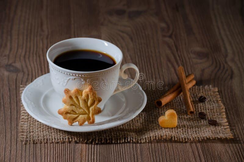 Чашка кофе и печенья любят лист и сердце с циннамоном, кофейными зернами на деревянном столе стоковое изображение rf