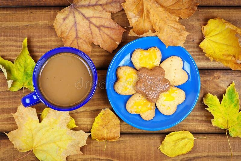 Чашка кофе и печенья с высушенными листьями осени стоковые фотографии rf