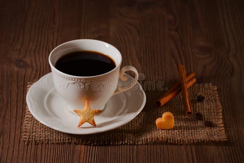 Чашка кофе и печенья любят звезда, циннамон, кофейные зерна на деревянном столе на темной предпосылке стоковая фотография