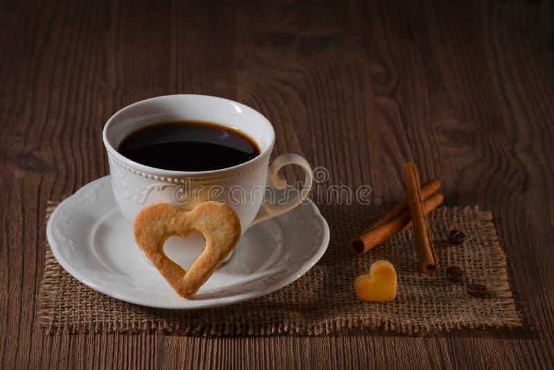 Чашка кофе и печенья любят сердце, циннамон, кофейные зерна на деревянном столе на темной предпосылке стоковое фото