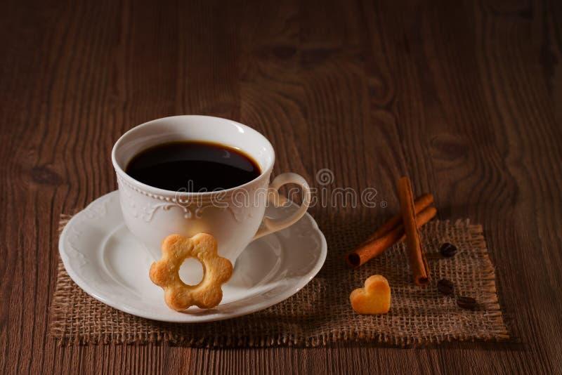 Чашка кофе и печенья любят цветок, циннамон, кофейные зерна на деревянном столе на темной предпосылке стоковые изображения rf