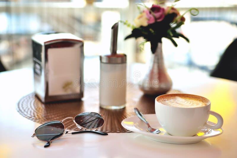 Чашка кофе и стекла на таблице в нерезкости солнечного света утра кафа стоковая фотография rf