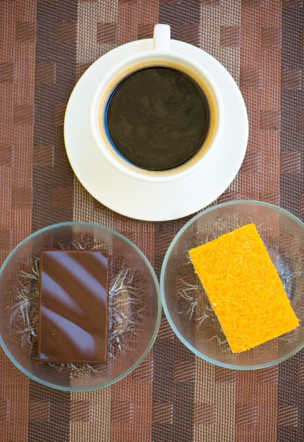 Чашка кофе и шоколад и золотые потоки испекут стоковое фото