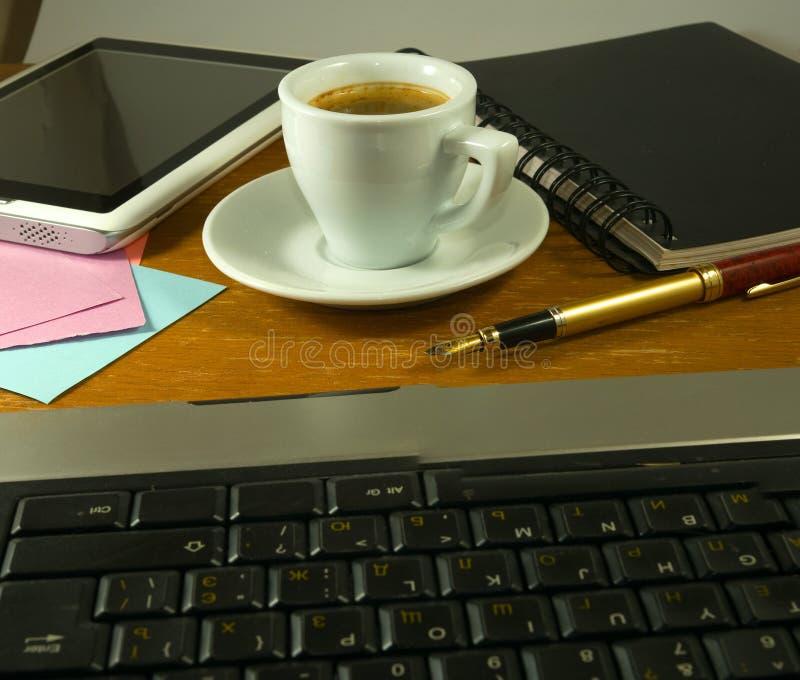 чашка кофе, канцелярские принадлежности, клавиатура и таблетка на крупном плане таблицы стоковая фотография rf