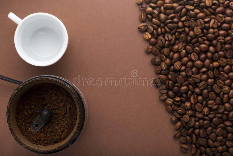 Чашка кофе, механизм настройки радиопеленгатора и фасоли на коричневом цвете стоковые изображения