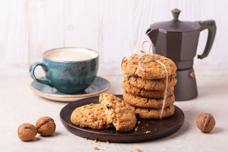 Чашка кофе, печенья овсяной каши, кофеварка на белой деревянной предпосылке стоковая фотография rf