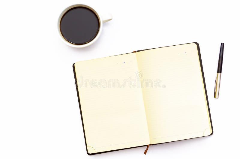 Чашка кофе, раскрывает дневник и пишет на белой предпосылке Минимальная концепция дела места службы в офисе стоковое фото rf