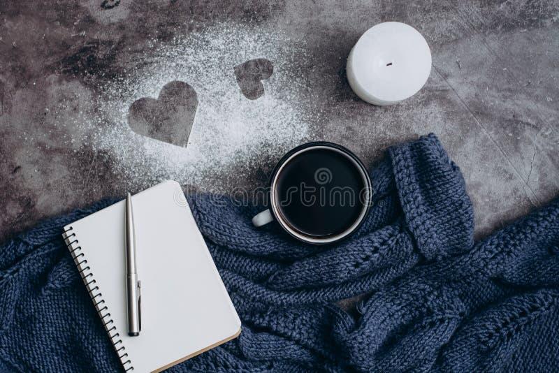Чашка кофе, свеча, тетрадь, ручка и теплый шерстяной свитер на серой таблице стоковое изображение rf