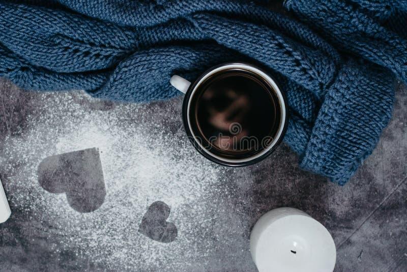 Чашка кофе, свеча, тетрадь, ручка и теплый шерстяной свитер на серой таблице стоковые фото