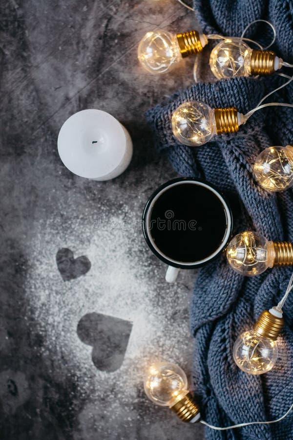 Чашка кофе, свеча, тетрадь, ручка и теплый шерстяной свитер, украшенные со светами приведенными на серой таблице стоковые фотографии rf