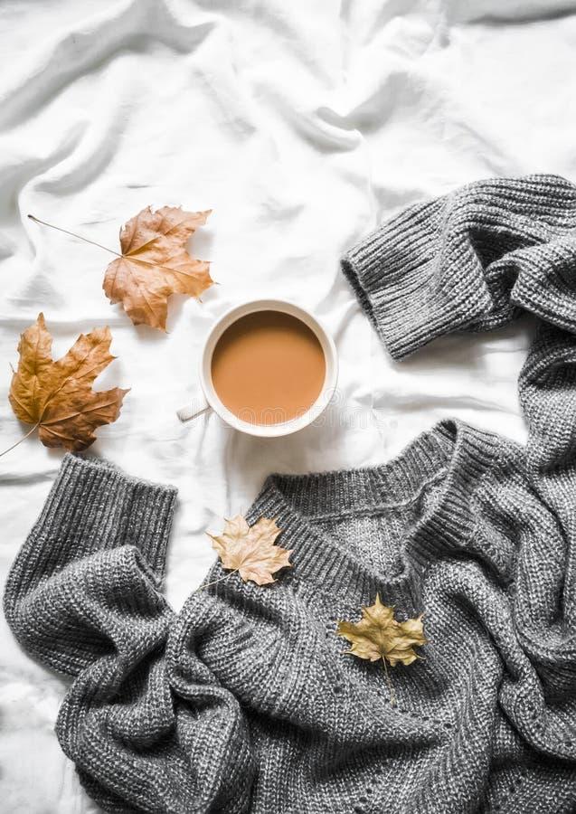 Чашка кофе, серая греет связанный свитер сверхразмерный, желтый сушит листья на кровати - уютном домашнем натюрморте стоковое фото