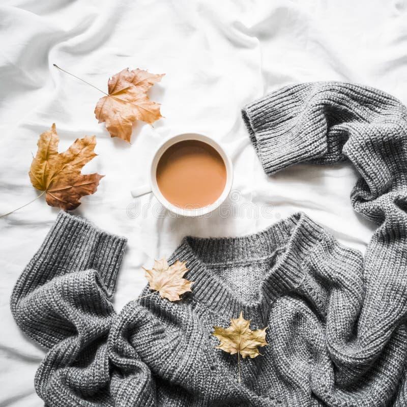 Чашка кофе, серая греет связанный свитер сверхразмерный, желтый сушит листья на кровати - уютном домашнем натюрморте стоковые фотографии rf