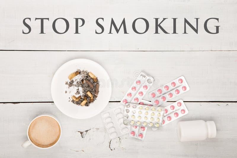 Чашка кофе, сигареты, медицинские бутылки и таблетки и текст останавливают курить стоковое фото rf