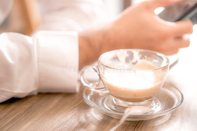 чашка кофе с горячим латте на деревянном столе с бизнесменом, наблюдающим сокаил-медиа на смартфоне в кафе и копировавшим простра стоковые изображения
