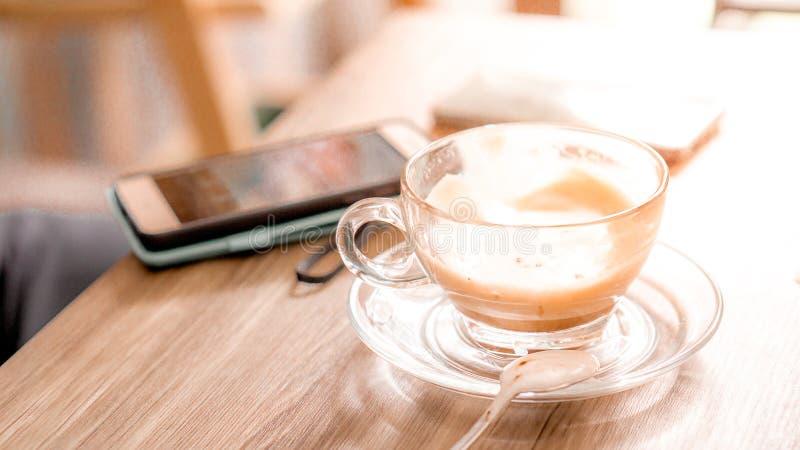 чашка кофе с горячим латте на деревянном столе с фоном смартфона в кафе и копировать пространство стоковые фотографии rf