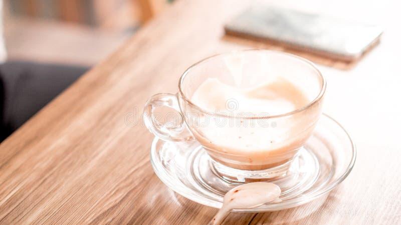 чашка кофе с горячим латте на деревянном столе с фоном смартфона в кафе и копировать пространство стоковое фото