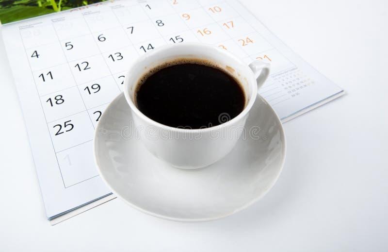Чашка кофе с календарем стены на белизне стоковое изображение rf