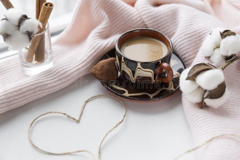 Чашка кофе с конфетой, сердце веревочки, хворостин хлопка, ручек циннамона на розовом связанном свитере стоковое изображение