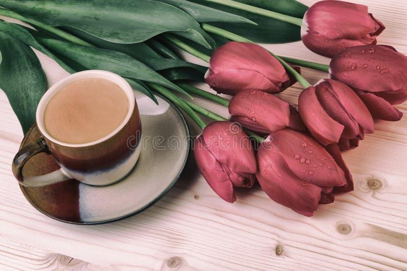 Чашка кофе с красными тюльпанами на кофе деревянного стола в винтажном стиле стоковое изображение rf